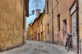 stock photo of porphyry  - View of ancient narrow street in Italy with bicycle lamp and bell tower - JPG