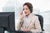 Angry businesswoman shouting in headset in bright office