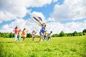 foto of kites  - Kids boys and girls with kite running in the par on sunny summer day - JPG