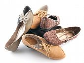 stock photo of flat-foot  - Pile of various female flat shoes isolated over white - JPG