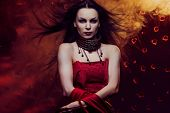foto of pale skin  - Beautiful vampire woman in red dress with waving hair - JPG