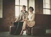 stock photo of passenger train  - Beautiful vintage style young couple with suitcases on a train station - JPG