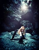 stock photo of cave  - Sexy Woman with dragon in a cave - JPG