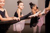 foto of ballet barre  - Cute little ballet dancers practicing some dance moves in a barre in a dance class - JPG