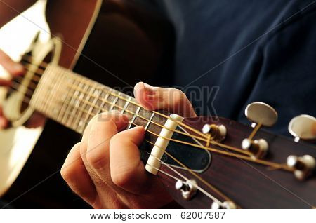 Hands of a person playing an acoustic guitar close up
