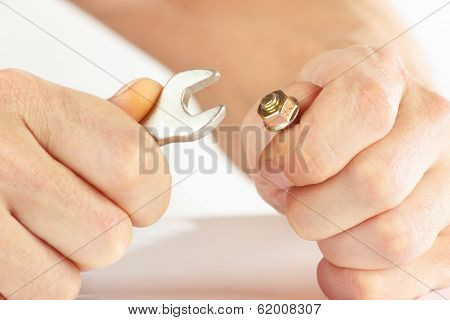 Hand of worker with a wrench to tighten the nut