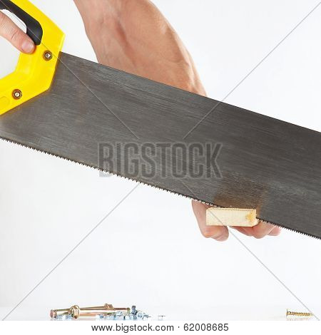 Hand of a joiner cutting a wooden block with a handsaw