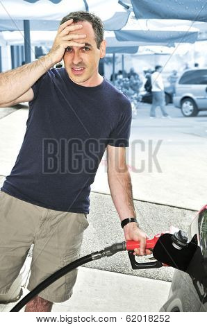 Man filling up a car at a gas station looking horrified