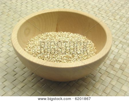 Wooden Bowl With Quinoa On Rattan Underlay