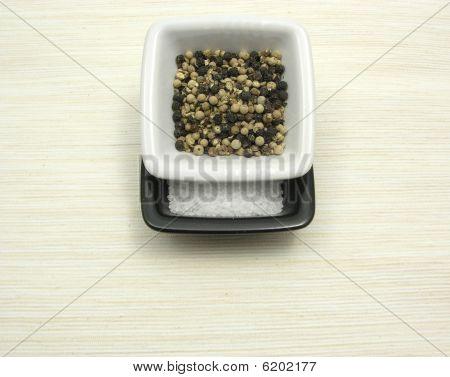 Tigelas de porcelana com pimenta e sal na subjacência bege