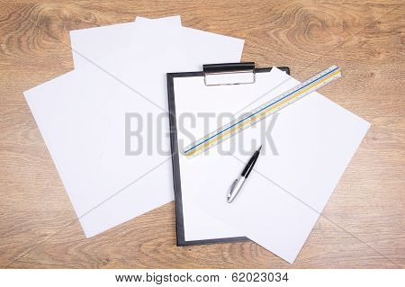 Clipboard, Pen, Straightedge And Paper On The Table