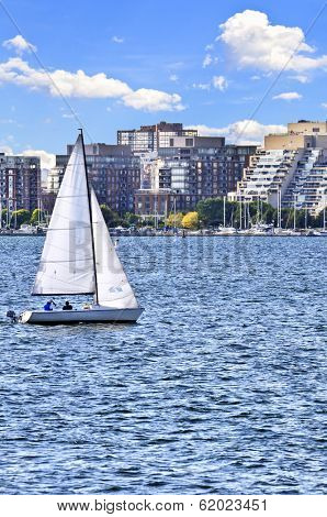 Sailboat sailing in Toronto harbor with scenic waterfront view