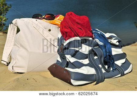Summer beach bags on sand with towels and sunglasses