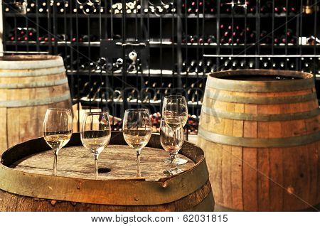 Row of wine glasses on barrel in winery cellar