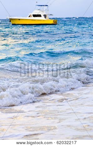 Waves breaking on tropical beach with boat in the distance