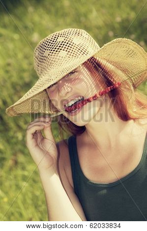 young woman eating wild strawberries