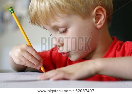 Young Child Drawing With Paper And Pencil