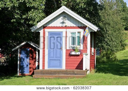 Red and white playhouse in a garden.