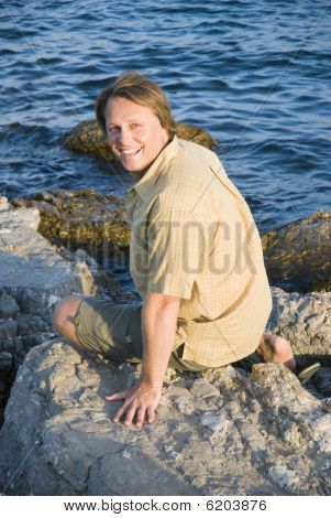 happy smiling forties man sitting on rocks.