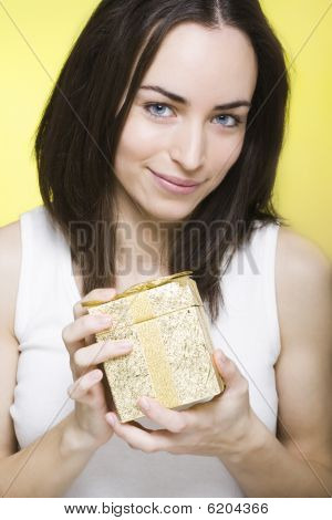 Young Woman Presenting A Nice Golden Shinny Gift Box