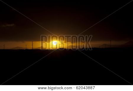 Sunset landscape behind a panorama of powerlines.