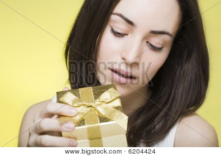 Young Woman Opens A Golden Shiny Gift Box