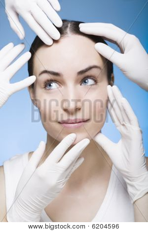 Many Rubber Gloves Touching The Face Of A Young Woman