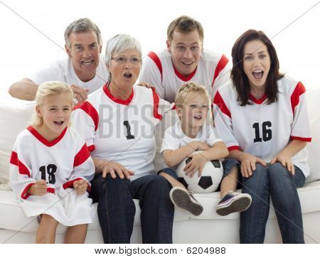 Excited Family Watching A Football Match In Television