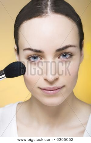 Jovem mulher pós sua pele com um pincel de maquiagem