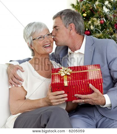 Senior Man Giving A Kiss And A Christmas Present To His Wife