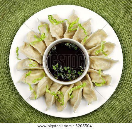 Plate of steamed dumplings with soy sauce from above