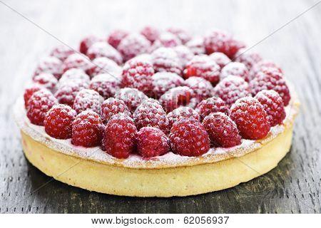 Fresh dessert fruit tart covered in raspberries