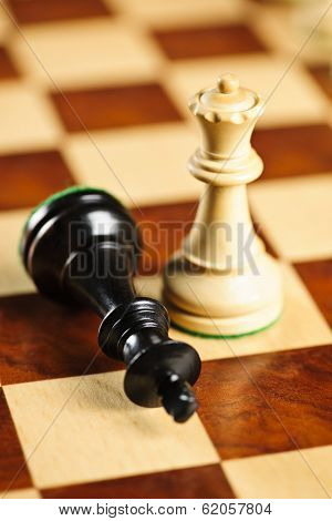 Closeup of checkmate on king by queen winning in chess game
