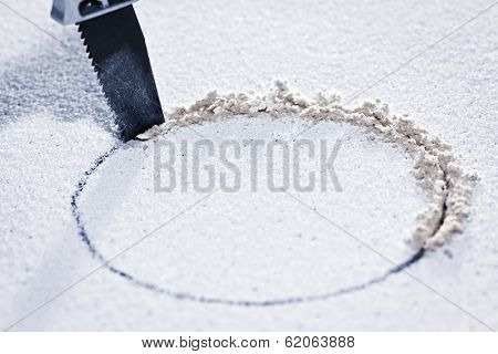 Handsaw cutting circular hole in ceiling tile
