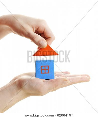 Hand building wooden block toy house isolated on white background