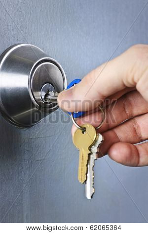 Hand inserting keys in door lock close up