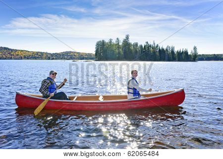 Family canoeing on sunny Lake of Two Rivers, Ontario, Canada
