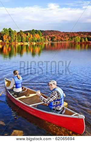 People canoeing on scenic lake in fall, Algonquin park, Canada