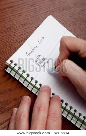 Hands Writing A Shopping List