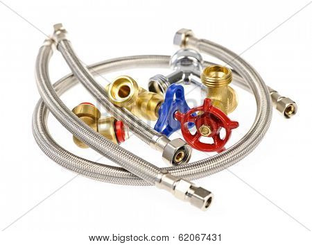 Pile of plumbing valves hoses and assorted parts isolated on white background