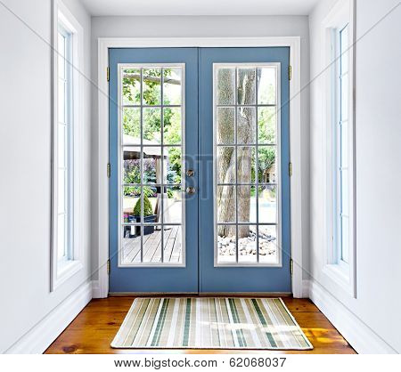 Double patio french doors with windows exiting to sunny backyard