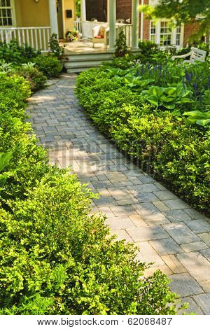 Paved stone path in lush green home garden