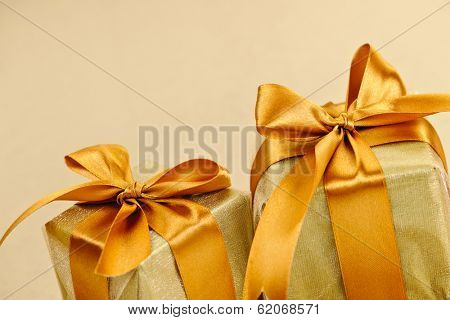 Two gift boxes wrapped in gold ribbons with copy space