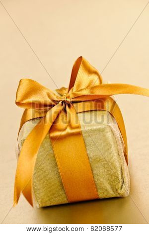 Gift box in gold wrapping paper with ribbon and bow