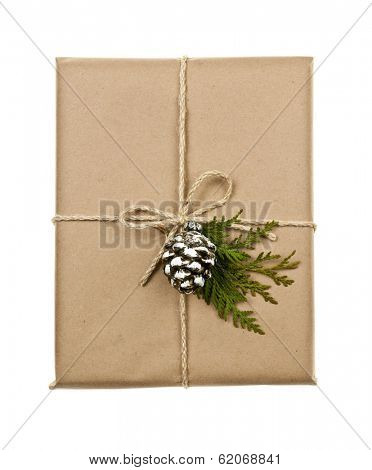 Christmas gift in brown wrapping and string with pine cone decoration isolated on white