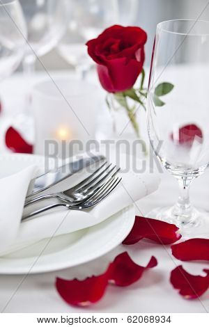 Romantic table setting with rose petals plates and cutlery
