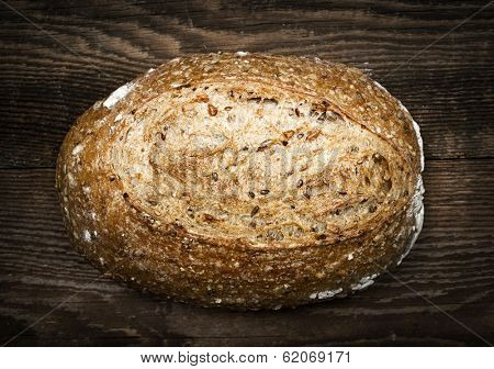 Artisan loaf of freshly baked multigrain bread on wooden background