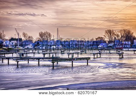 Sunset behind floating homes at Bluffers park marina in Toronto, Canada.  Winter.