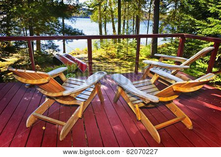 Wooden deck of cottage with Adirondack chairs at lake