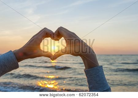 Hands and fingers in heart shape framing setting sun at sunset over ocean